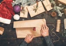 供以人员手在本文的被包裹的圣诞节礼物 免版税库存照片