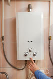 供以人员手开关气体水加热器对热水 库存图片