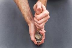 供以人员手雕刻有勾子刀子的一把木匙子在灰色背景 库存照片