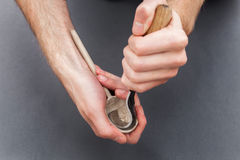 供以人员手雕刻有勾子刀子的一把木匙子在灰色背景 免版税图库摄影
