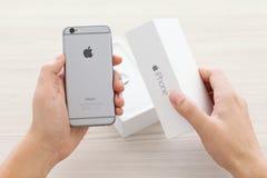 供以人员打开新的电话iPhone 6空间灰色 免版税库存图片