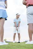 供以人员打高尔夫球反对与站立在前景的朋友的天空 免版税库存照片