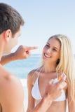 供以人员把太阳奶油放在逗人喜爱的女朋友鼻子上 免版税库存图片