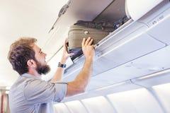 供以人员把行李放在飞机的架子顶部上 免版税库存照片