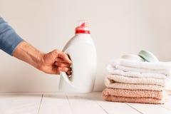 供以人员投入在一个瓶子洗涤的胶凝体穿衣的桌的` s手 以堆毛巾和肥皂为背景 免版税库存照片