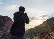 供以人员拍在山的照片,当日落 库存图片