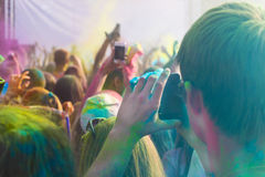 供以人员拍在手机的照片在holi颜色节日 图库摄影