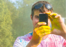 供以人员拍在手机的照片在holi颜色节日 库存照片