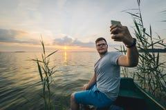 供以人员拍在日出他的电话的照片,当坐在老小船时 免版税库存照片