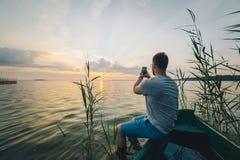 供以人员拍在日出他的电话的照片,当坐在老小船时 库存照片
