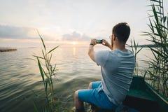 供以人员拍在日出他的电话的照片,当坐在老小船时 免版税库存图片
