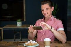 供以人员拍摄在桌上的食物在咖啡店 图库摄影