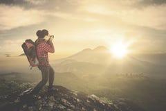 供以人员拍日出视图照片在山的 图库摄影