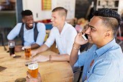 供以人员拜访智能手机和喝啤酒在酒吧 库存图片
