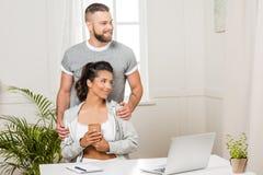 供以人员拥抱有咖啡的妇女在与膝上型计算机的桌上 库存照片