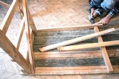供以人员拧紧螺丝入木头 库存图片