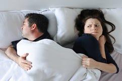 供以人员拱起从妇女的毯子在床上 图库摄影