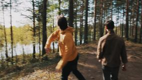 供以人员拾起岩石并且投掷它入湖,当走在有朋友的时森林里 股票录像