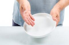供以人员拿着一个空的盘在表明他的手上没有conten 库存图片