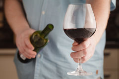 供以人员拿着一块玻璃用红葡萄酒和瓶 库存图片