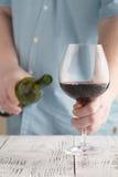 供以人员拿着一块玻璃用红葡萄酒和瓶 免版税图库摄影