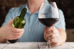 供以人员拿着一块玻璃用红葡萄酒和瓶 库存照片