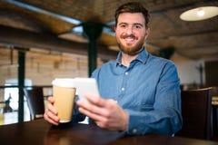 供以人员拿着一次性咖啡杯和手机 免版税图库摄影