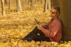 供以人员拿着一种数字式片剂和倾斜反对树 免版税库存照片