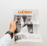 供以人员拿着与伊曼纽尔Macron的十字架报报纸第一个pag的 免版税图库摄影