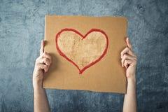 供以人员拿着与心脏形状图画的纸板纸 免版税库存图片