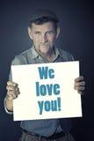 供以人员拿着与我们爱您的词的标志 免版税库存照片