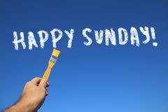 供以人员拿着与文本愉快的星期天的手画笔 免版税库存图片