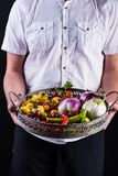 供以人员拿着与新鲜蔬菜的一个金属篮子 图库摄影