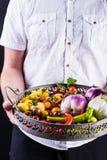 供以人员拿着与新鲜蔬菜的一个金属篮子 免版税图库摄影
