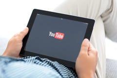 供以人员拿着与app YouTube的iPad在屏幕上 库存照片