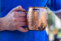 供以人员拿着在一个明亮的满身是汗的铜杯子的一头冷的莫斯科骡子 图库摄影