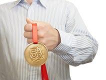 供以人员拿着在一条红色丝带的一枚奖牌 库存照片