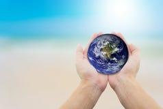 供以人员拿着地球用在海滩背景的手 库存照片