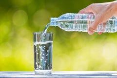 供以人员拿着塑料瓶装水和倾吐水的` s手入在木桌上的玻璃在被弄脏的绿色bokeh背景 免版税库存照片