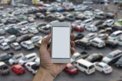供以人员拿着巧妙的电话和室外停车处的空的屏幕手 免版税库存图片