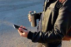 供以人员拿着手机和热杯子,旅行杯子 免版税库存图片
