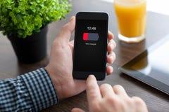 供以人员拿着有低落被充电的电池的电话在屏幕上 免版税图库摄影