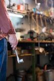 供以人员拿着有棘轮的` s手一把插口金属板钳在雀鳝 库存照片