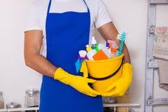 供以人员拿着有瓶和刷子的,手套塑料桶和 免版税库存照片