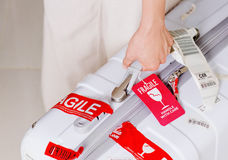 供以人员拿着有红色行李标记的手提箱易碎在机场 免版税图库摄影