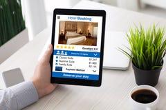供以人员拿着有app旅馆预定屏幕的手计算机片剂 库存照片