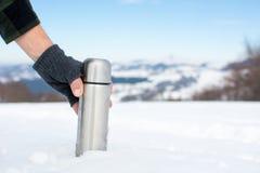 供以人员拿着热水瓶在一座多雪的山 库存图片