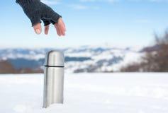 供以人员拿着热水瓶在一座多雪的山 免版税库存照片