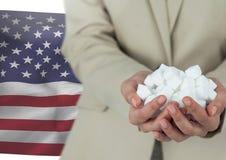 供以人员拿着纸在他的手上反对美国国旗 库存图片