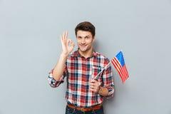 供以人员拿着美国旗子和显示好标志 免版税库存图片